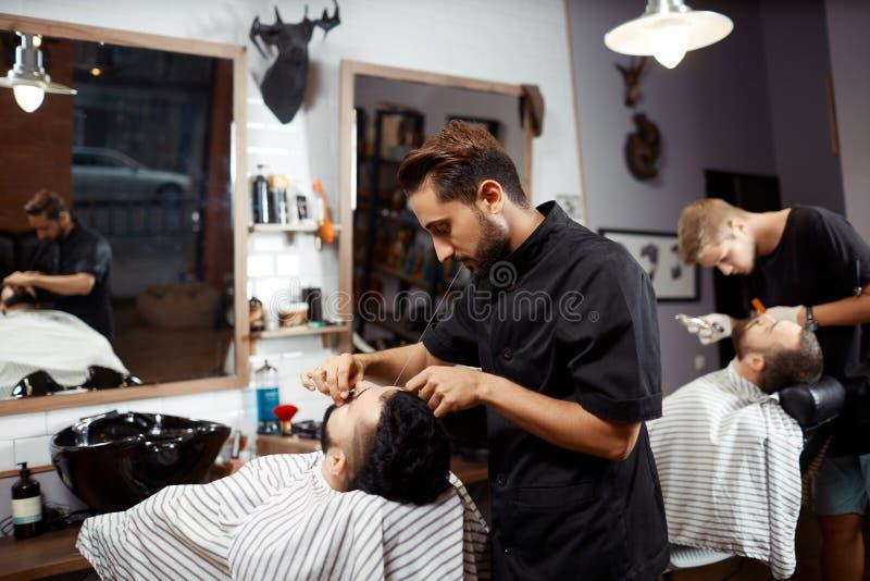 Barbeiro que trabalha com o cliente na cadeira foto de stock royalty free