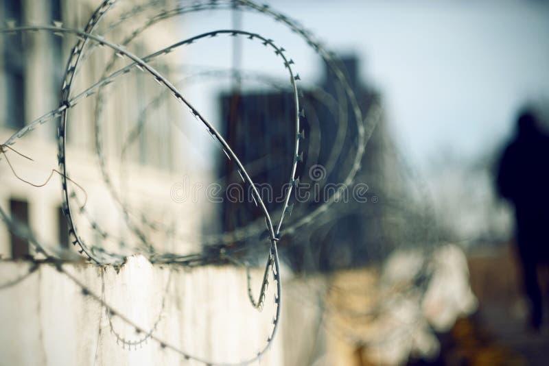Barbelé pointu en haut de la barrière et de la figure foncée du prisonnier photographie stock