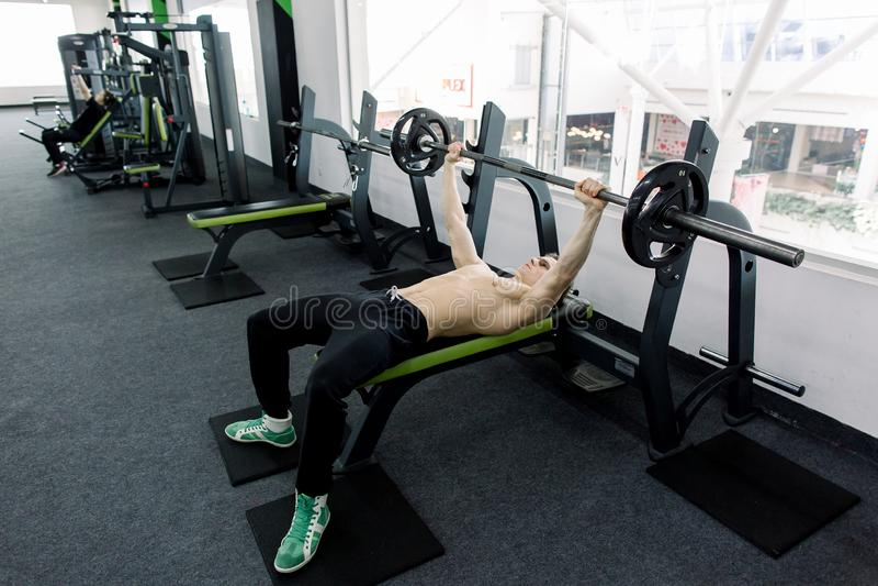 Barbell de elevación del hombre caucásico muscular joven en el banco en el gimnasio foto de archivo