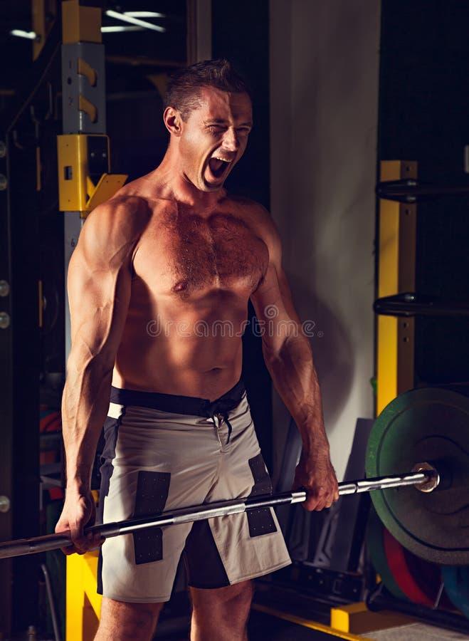 Barbell de elevación enérgico del hombre fuerte en gimnasio del crossfit y grito agresivo ruidoso en fondo oscuro de club de depo imagen de archivo