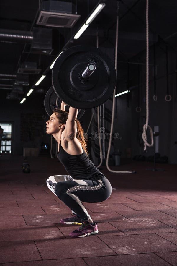 Barbell de elevación de la mujer fuerte como parte de la derrota del ejercicio del crossfit imágenes de archivo libres de regalías