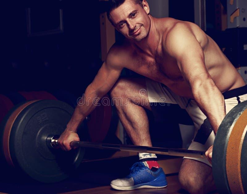 Barbell de elevación sonriente hermoso del hombre brutal en gimnasio del crossfit en d fotografía de archivo