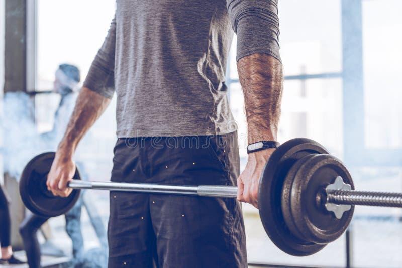 Barbell de levage de sportif musculaire à la séance d'entraînement de gymnase image stock