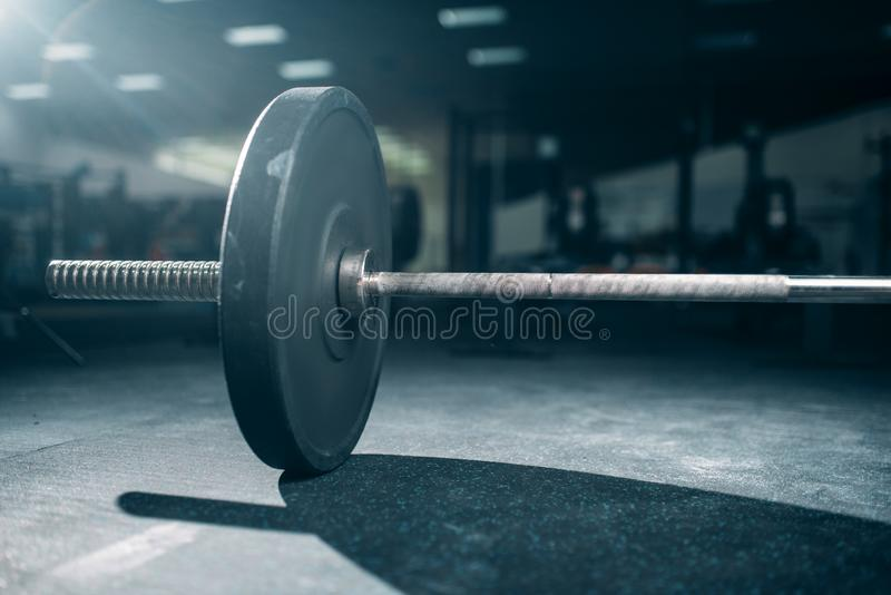 Barbell on the floor in gym closeup view, nobody. Weightlifting sport concept, heavy weights stock photography