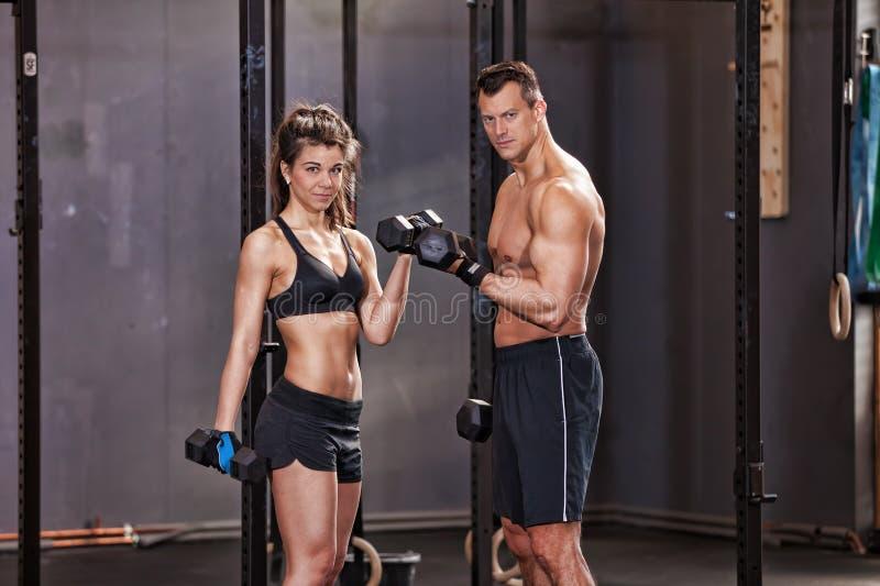 Barbell opleidende man en vrouw in een gymnastiek stock fotografie