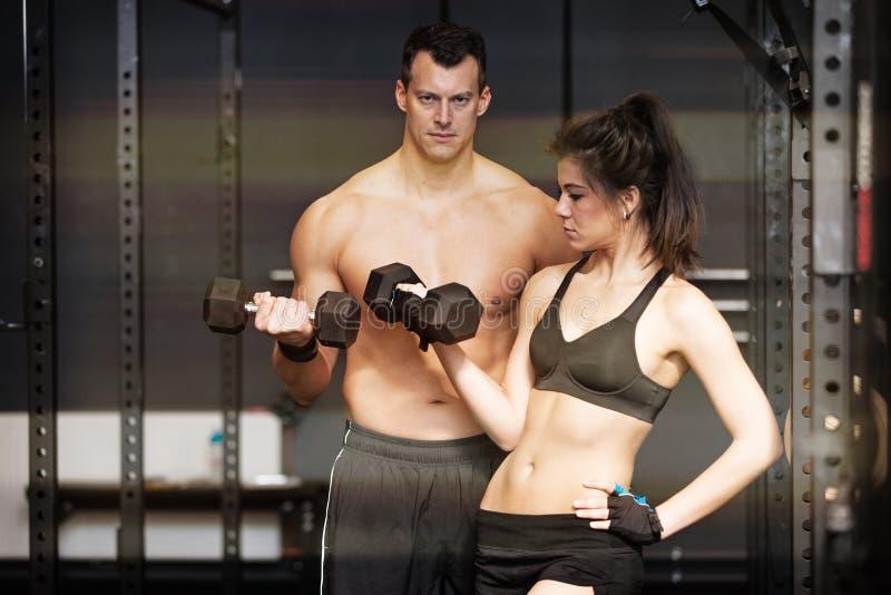 Barbell opleidende mens en womanin een gymnastiek stock afbeelding