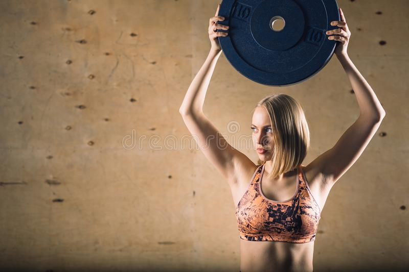 Barbell plate raise blonde girl workout at gym exercise stock photography