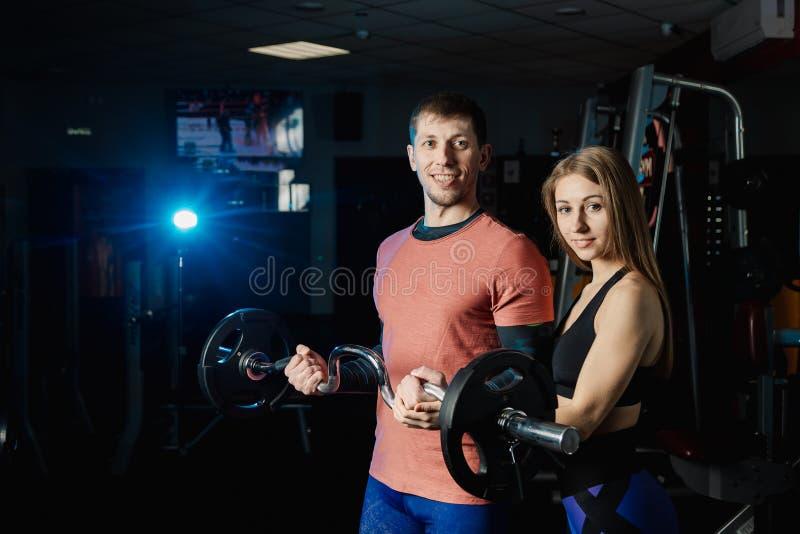 Barbell sportif beau de biceps de formation d'homme dans le gymnase avec l'aide d'un entraîneur féminin photo stock