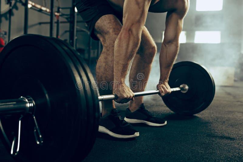 Barbells de elevación aptos del hombre joven que se resuelven en un gimnasio imagen de archivo