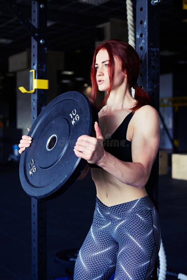 Barbells de elevación del atleta resuelto que parecen enfocados fotografía de archivo