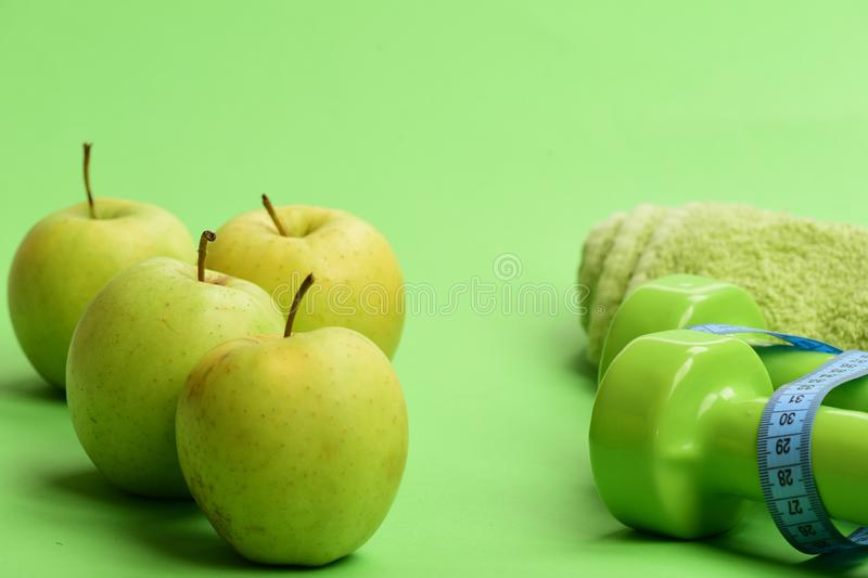 Barbells by juicy green apples. Sports regime equipment, copy space. Dumbbells in bright green color, measure tape, towel and fruit on green background royalty free stock photography