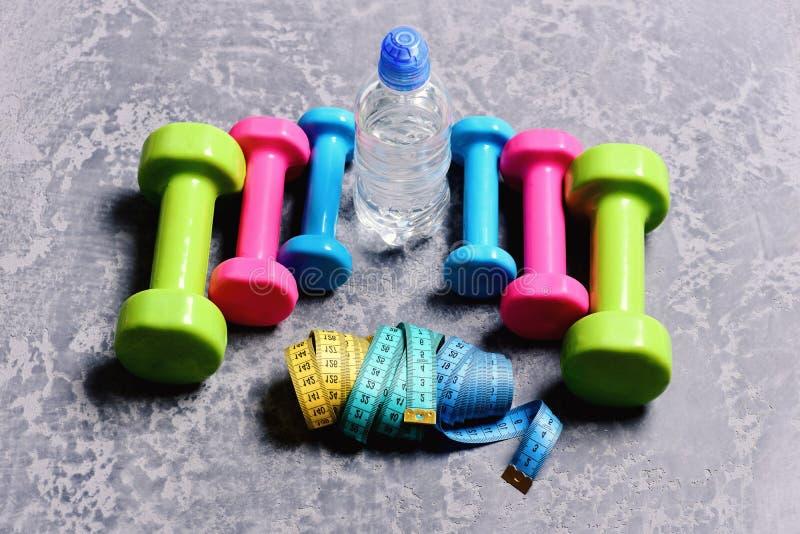 Barbells, kolorowe taśm miary i bidon umieszczający w wzorze, fotografia stock