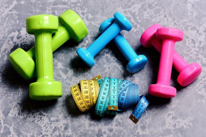 Barbells, kolorowe taśm miary i dumbbells umieszczający w wzorze, zdjęcie royalty free