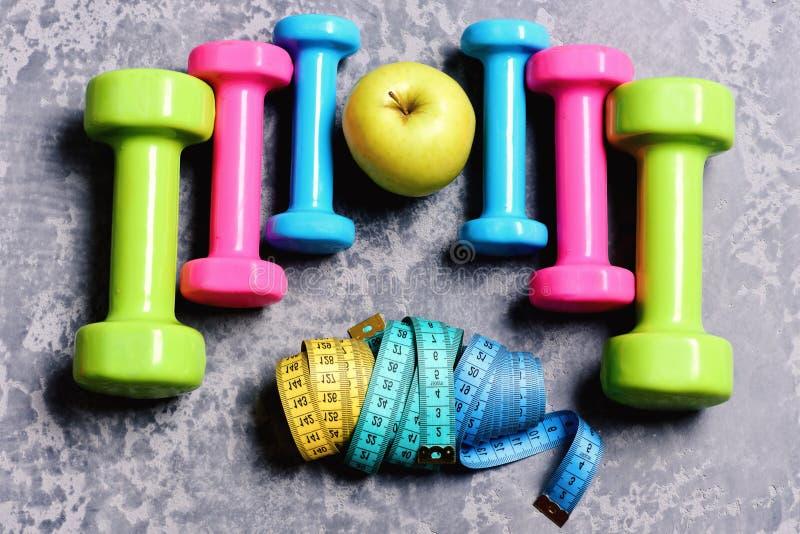 Barbells, kolorowe taśm miary i jabłko umieszczający w wzorze, topview fotografia royalty free