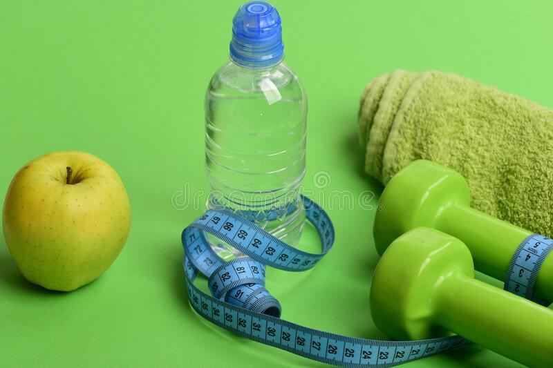 Barbells near juicy green apple. Dumbbells in bright green color stock photos