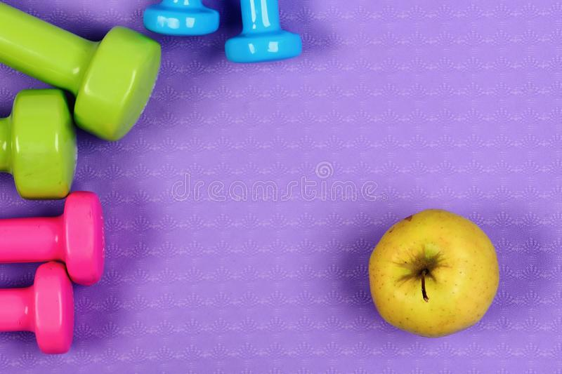 Barbells in pink, green and blue colors near apple fruits stock images