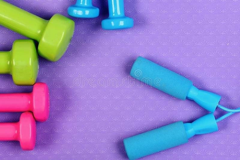 Barbells in pink, green and blue colors near skipping rope. Top view. Dumbbells and jump rope on purple texture background. Shaping and fitness equipment royalty free stock photography