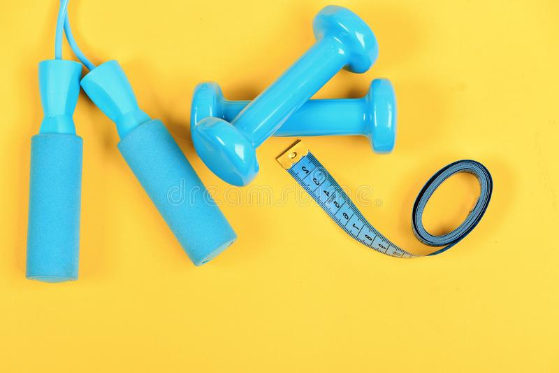 Barbells and skipping rope next to measure tape roll. Sports and healthy lifestyle concept. Dumbbells and jump rope in cyan color isolated on yellow background stock photography