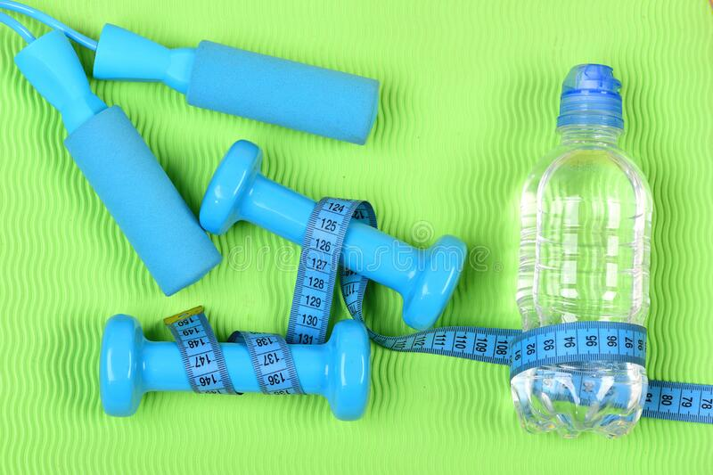 Barbells and skipping rope tied around with measuring tape roll stock images