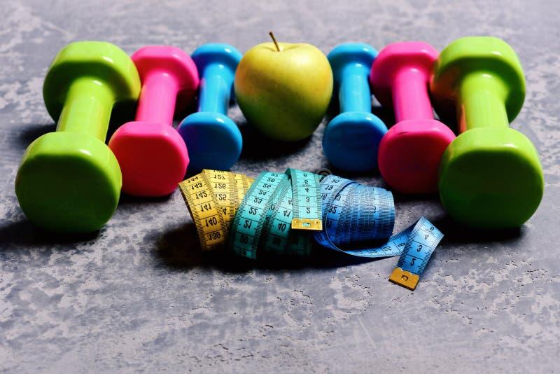Barbells, taśm miary i jabłko umieszczający w wzorze, zakończenie up fotografia stock