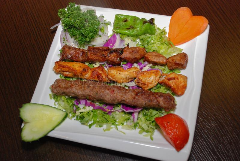 Barbequed chicken, lamb and kebab on the white plate royalty free stock images