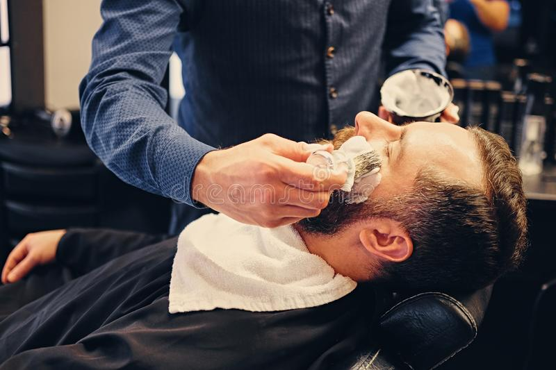 Barber applies shaving foam. To a man`s face in a saloon stock images