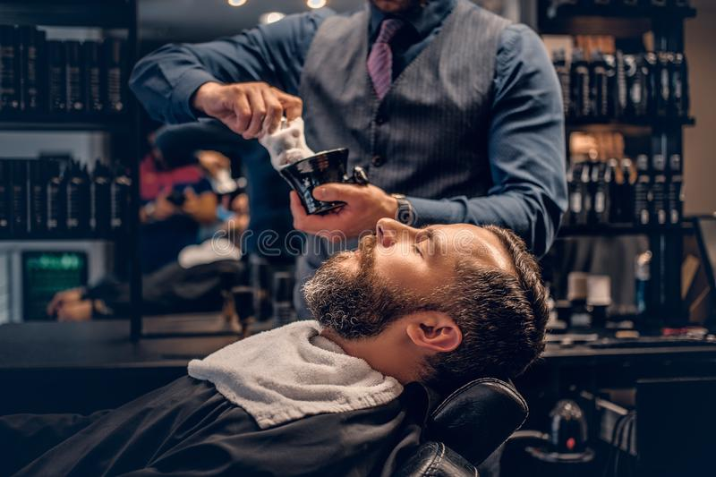 Barber applies shaving foam. To a man`s face in a saloon stock photo