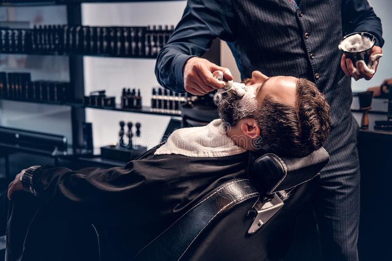 Barber applies shaving foam. To a man`s face in a saloon royalty free stock photo