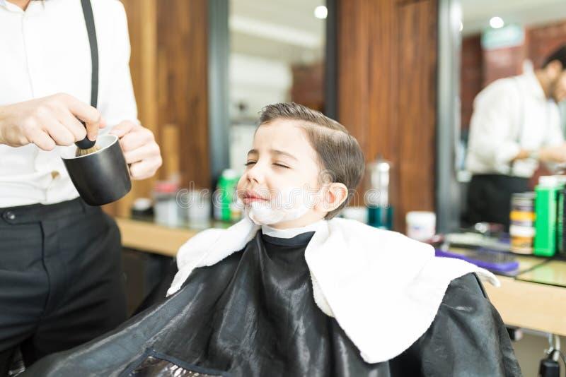 Barber Applying Shaving Foam On-Jongens` s Gezicht in Winkel stock foto