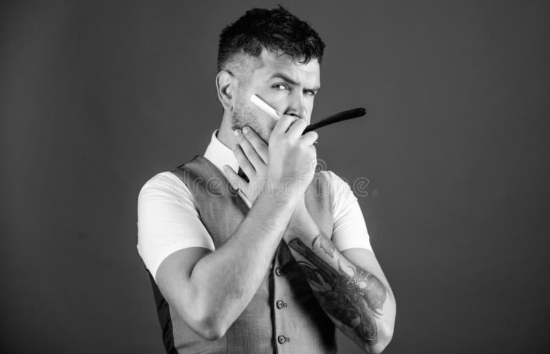 Barber art concept. Barber unshaven hipster with sharp danger straight razor. Barbershop hairdresser salon. Barber beard. Grooming tips. Man vest with bow tie royalty free stock image