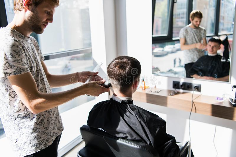 Barber in Barbershop cutting a client`s hair with an electric razor for fashionable hairstyle. stock photo