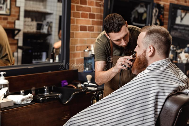 Barber and bearded man in barber shop royalty free stock photo