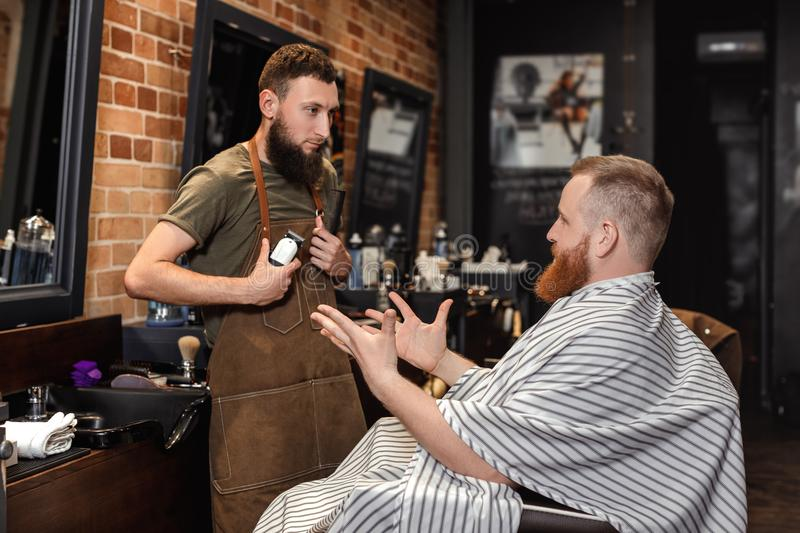 Barber and bearded man in barber shop royalty free stock photography