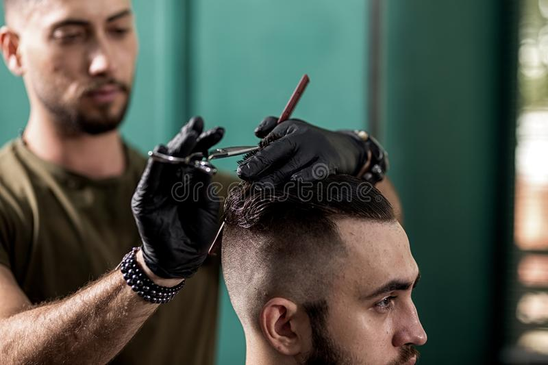 Barber in black gloves cuts with scissors hair of stylish man at a barbershop royalty free stock photos