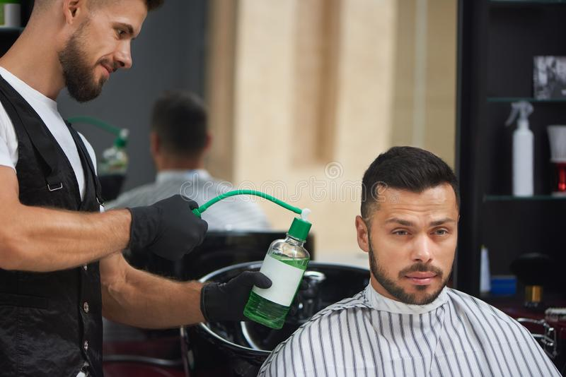 Barber in black gloves sprinkling green water on handsome man. royalty free stock photos