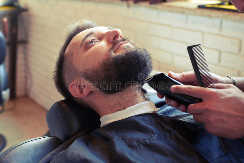 Barber with comb and electric razor. Barber shaving beard with electric razor and holding comb in barbershop stock images