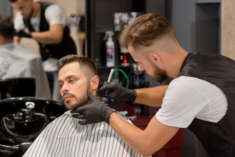 Barber concentrated on shaving man`s beard using sharp razor. royalty free stock photos