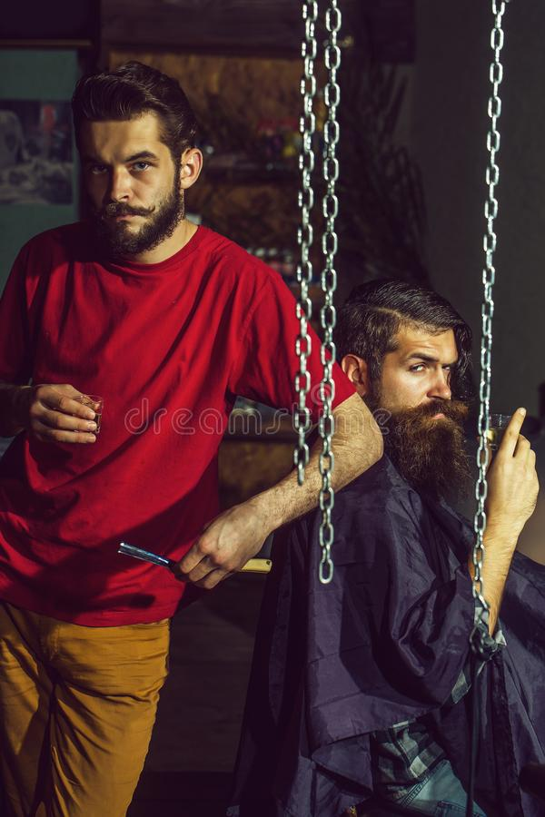 Barber and customer in barbershop. Two handsome men, bearded hipsters with beard and moustache drink vodka or alcohol. Barber and male customer in hairdressing royalty free stock photos