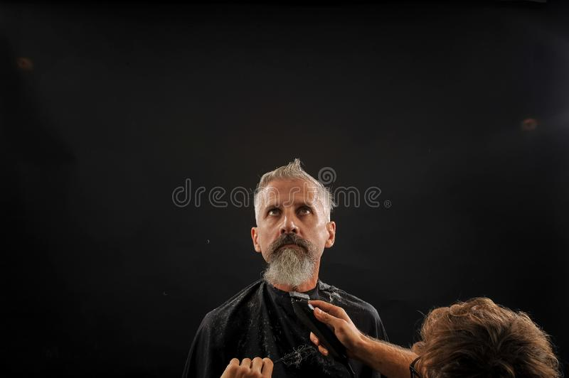 Barber cuts a beard to a client to an elderly gray-haired man stock photography