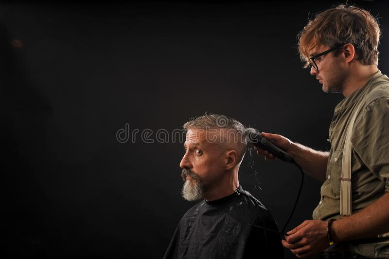 Barber cuts a beard to a client to an elderly gray-haired man royalty free stock photos