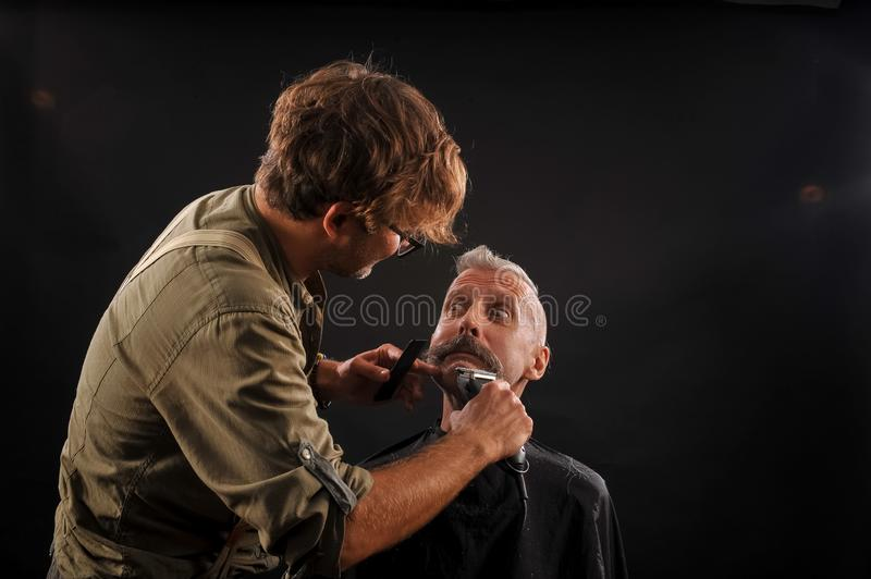 Barber cuts a beard to a client to an elderly gray-haired man stock photos