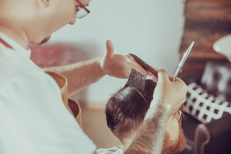 Barber cuts the client`s hair in his barber shop. Photo in vintage style stock photo