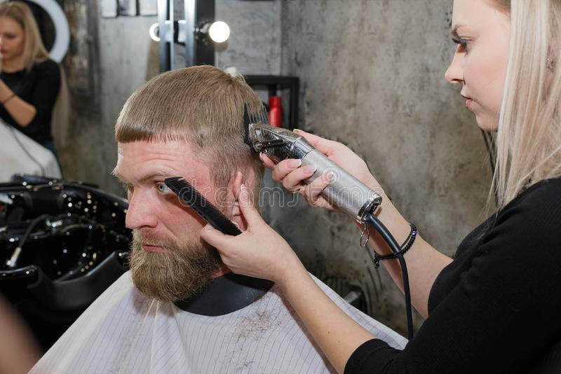 Barber hair cutting machine. The master provides a haircut. Barber cutting hair with clipper. Master provides service. The master makes a haircut with a machine royalty free stock photography