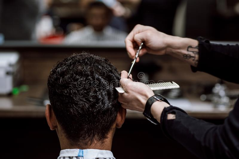The barber is cutting a man`s hair holding scissors and comb in his hands opposite the mirror in a barbershop royalty free stock photos