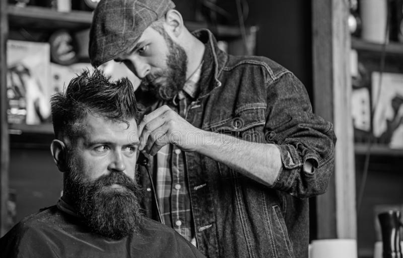 Barber in denim jacket busy with trimming hipster, barbershop background. Client with beard and mustache covered with. Cape. Barber work on haircut with hair stock images