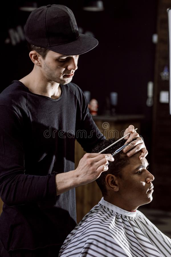 The barber dressed in black clothes is cutting a man`s hair holding scissors and comb in his hands in a barbershop stock photography