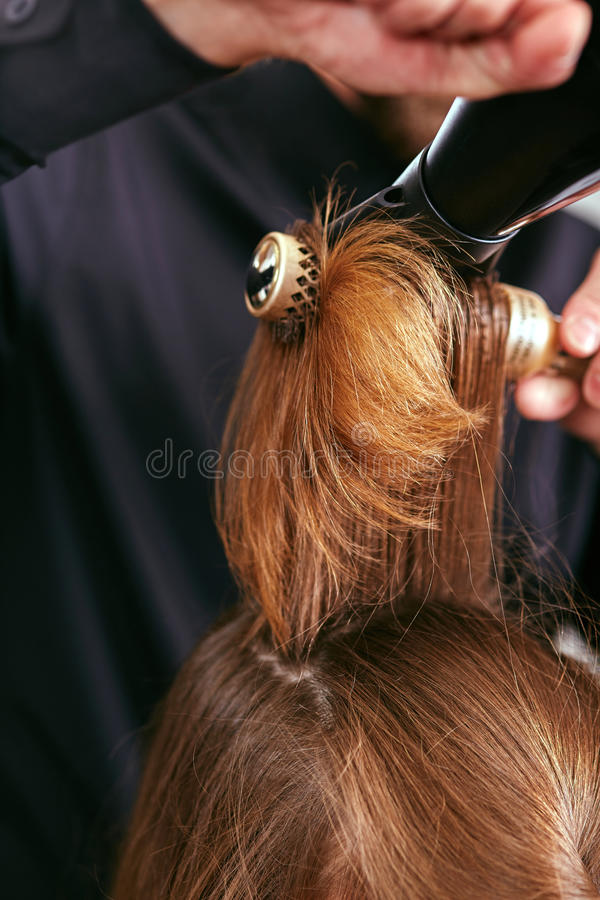 Barber dries the hair with the hair dryer of young, beautiful girl in a beauty salon royalty free stock photo