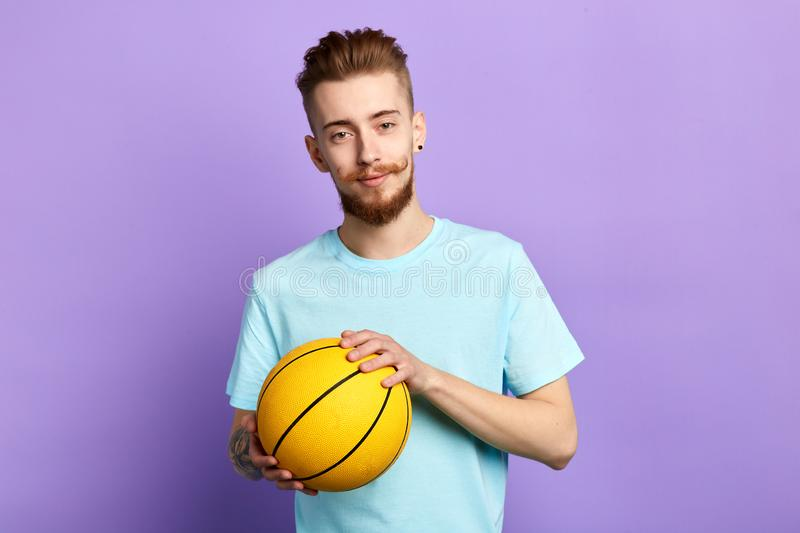 Barber is fond of sport. man is playing with a ball,. Handsome man with funny stylish moustache with a basket ball posing to the camera, entertainmnet, leisure stock photography