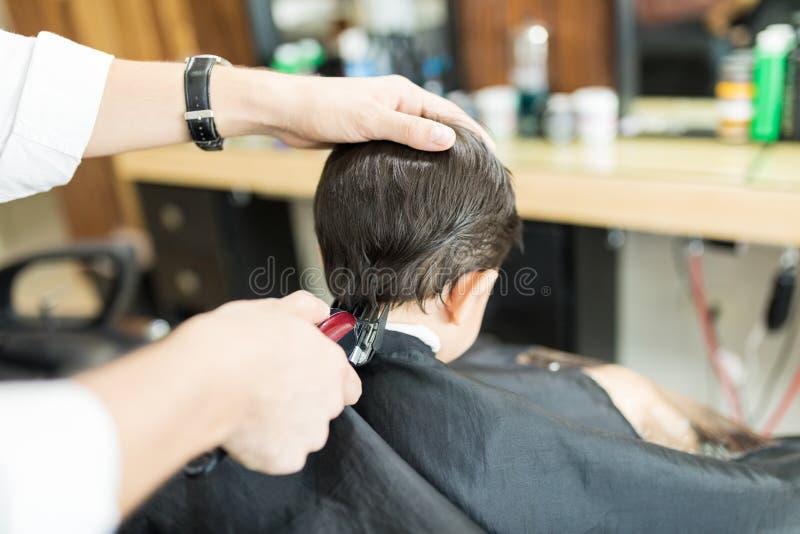 Barber Giving Haircut To Client che utilizza regolatore nel negozio immagini stock