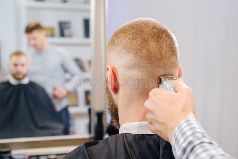 Barber goli głowę klienta czerwonym przycinaczem elektrycznym selektywna koncentracja obrazy royalty free